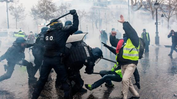PARIS, FRANCE - DECEMBER 01: Protesters clash with riot police at the Place de l'Etoile during a Yellow Vest protest on December 1, 2018 in Paris, France. The 'Yellow Vest' is a protest movement without political affiliation that rallies against taxes and rising fuel prices. (Photo by Etienne De Malglaive/Getty Images)