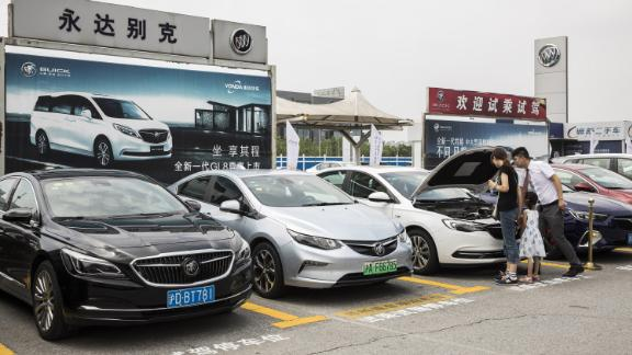 People look at a General Motors Co. (GM) Buick vehicles sitting parked outside a car dealership in Shanghai, China, on Sunday, July 8, 2018. The long threatened trade war escalated just after midnight in Washington on July 6 when the U.S. imposed tariffs on $34 billion of Chinese imports and Beijing immediately said it would be forced to retaliate. Photographer: Qilai Shen/Bloomberg via Getty Images