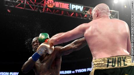 Tyson Fury punches Deontay Wilder in the fifth round.