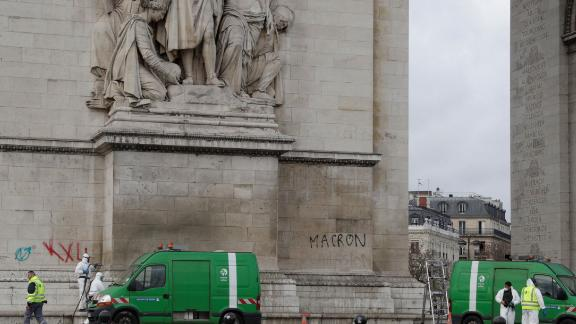 Workers clean grafitti off the Arc de Triomphe.