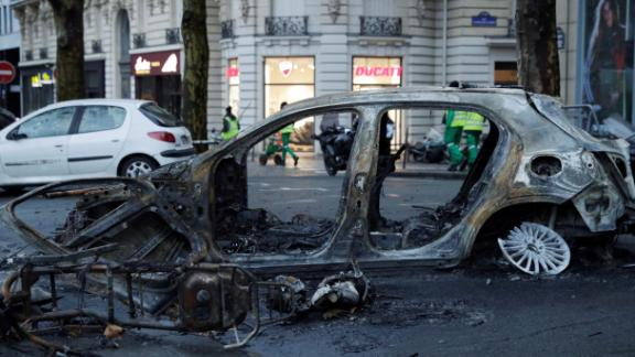 A burned-out car sits in a Paris street the day after riots spread through the city.