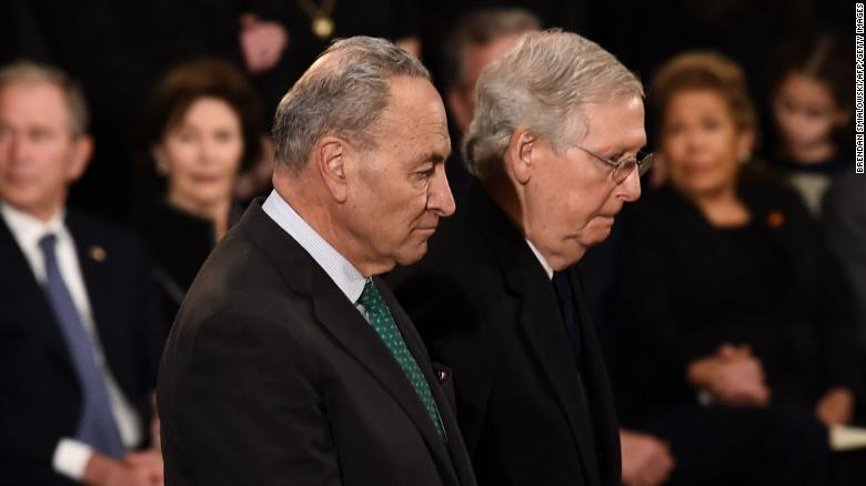 Senate Majority Leader Mitch McConnell, at right, and US Senate Minority Leader Chuck Schumer, at left, pay their respects during the service for former US President George H.W. Bush as he lies in state at the US Capitol during a ceremony in Washington, DC. (Photo by Brendan SMIALOWSKI / AFP)