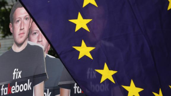 Cutouts of Facebook Inc. Chief Executive Officer Mark Zuckerberg stand beside a European Union (EU) flag during a protest outside the Berlaymont building ahead of his testimony before lawmakers in Brussels, Belgium, on Tuesday, May 22, 2018. Zuckerberg will tout the companys investment in Europe and again take responsibility for privacy failures, according to testimony prepared for an appearance Tuesday in front of the regions parliament. Photographer: Dario Pigantelli/Bloomberg via Getty Images