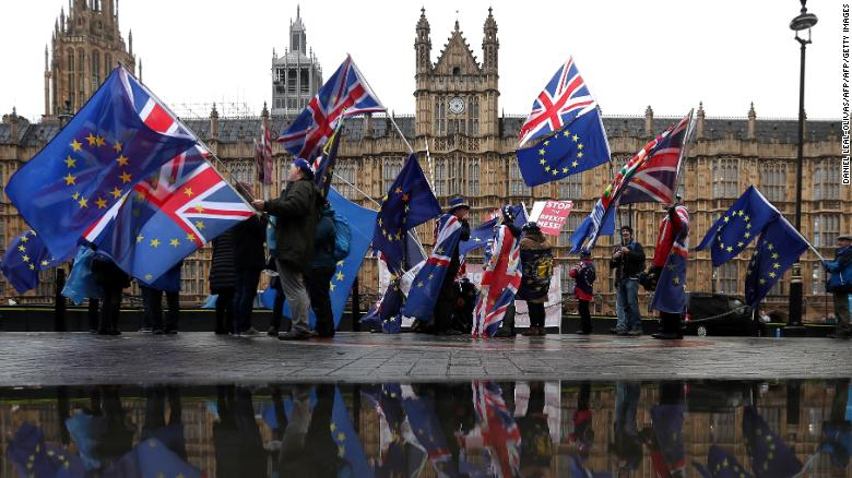 Anti-Brexit protesters wave EU flags outside Parliament.