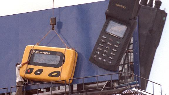 This 1998 file photo shows a worker installing an oversized copy of a pager on a billboard in Phnom Penh, Cambodia.