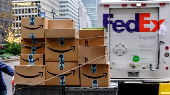 A worker pushes Amazon.com Inc. packages in front of a FedEx Corp. delivery truck in New York, U.S., on Monday, Nov. 26, 2018. Americans spent $50.6 billion online this month through S