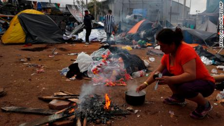 A woman makes instant coffee over a campfire a day beside belongings soaked in rains which continued overnight, inside the Benito Juarez sports complex in Tijuana, Mexico, Friday, Nov. 30, 2018. Authorities in the Mexican city of Tijuana have begun moving some of more than 6,000 Central American migrants from an overcrowded shelter on the border to an events hall further away.(AP Photo/Rebecca Blackwell)