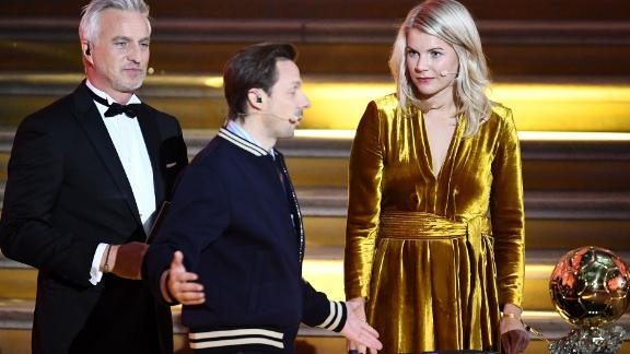Olympique Lyonnais' Norwegian forward Ada Hegerberg (R) looks on next to French former player and presenter David Ginola and French DJ and co-host Martin Solveig (C) after receiving the women's 2018  Women's Ballon d'Or award for best player of the year during the 2018 Ballon d'Or award ceremony at the Grand Palais in Paris on December 3, 2018. (Photo by FRANCK FIFE / AFP)        (Photo credit should read FRANCK FIFE/AFP/Getty Images)