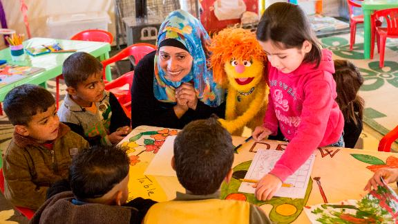 Ameena, a teacher, works with Tonton the muppet during a kindergarten class for Syrian refugee children at the Fneish camp in Lebanon.