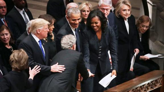 WASHINGTON, DC - DECEMBER 05:  Former U.S. President George W. Bush (C) leans across President Donald Trump and first lady Melania Trump to greet fellow former presidents Barack Obama, Bill Clinton and former first ladies Rosalynn Carter, Hillary Clinton and Michelle Obama during the state funeral for his father and former President George H.W. Bush at the National Cathedral December 05, 2018 in Washington, DC. A WWII combat veteran, Bush served as a member of Congress from Texas, ambassador to the United Nations, director of the CIA, vice president and 41st president of the United States.