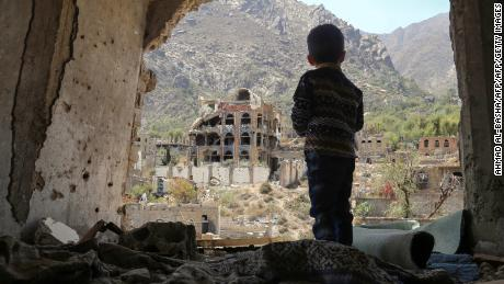 A Yemeni child looks at buildings damaged by an airstrike in the southern city of Taez.