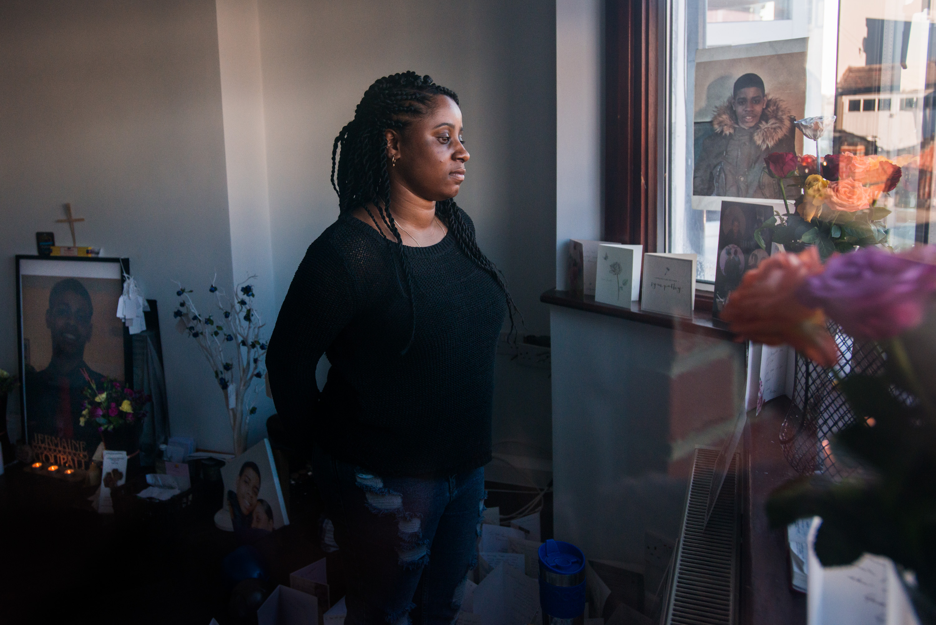 Goupall is seen through the window of her family's front room in Thornton Heath, south London. The room has become a shrine dedicated to honoring the life of her brother, Jermaine.
