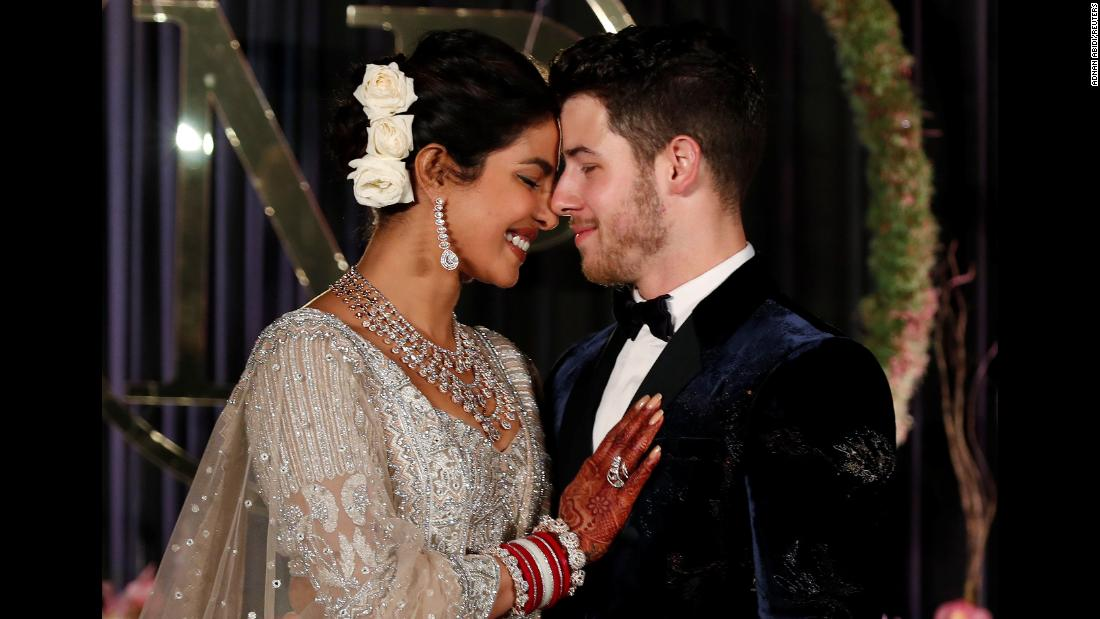 Actress Priyanka Chopra and her new husband, singer Nick Jonas, pose for photos at a wedding reception in New Delhi on Tuesday, December 4.