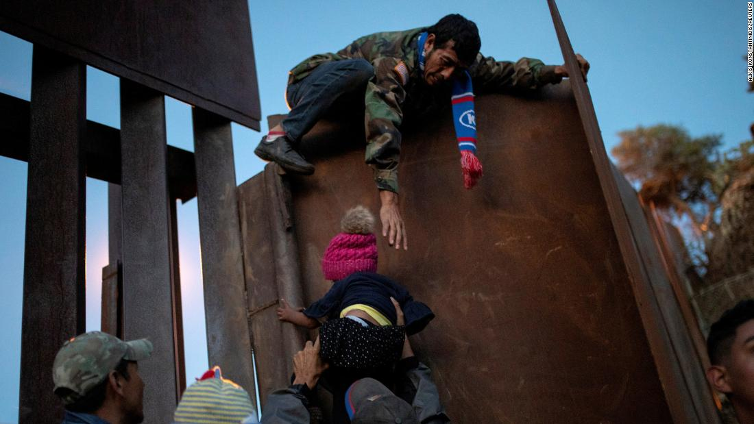 Migrants from Honduras try to scale a border fence in Tijuana, Mexico, to cross into the United States on Sunday, December 2.