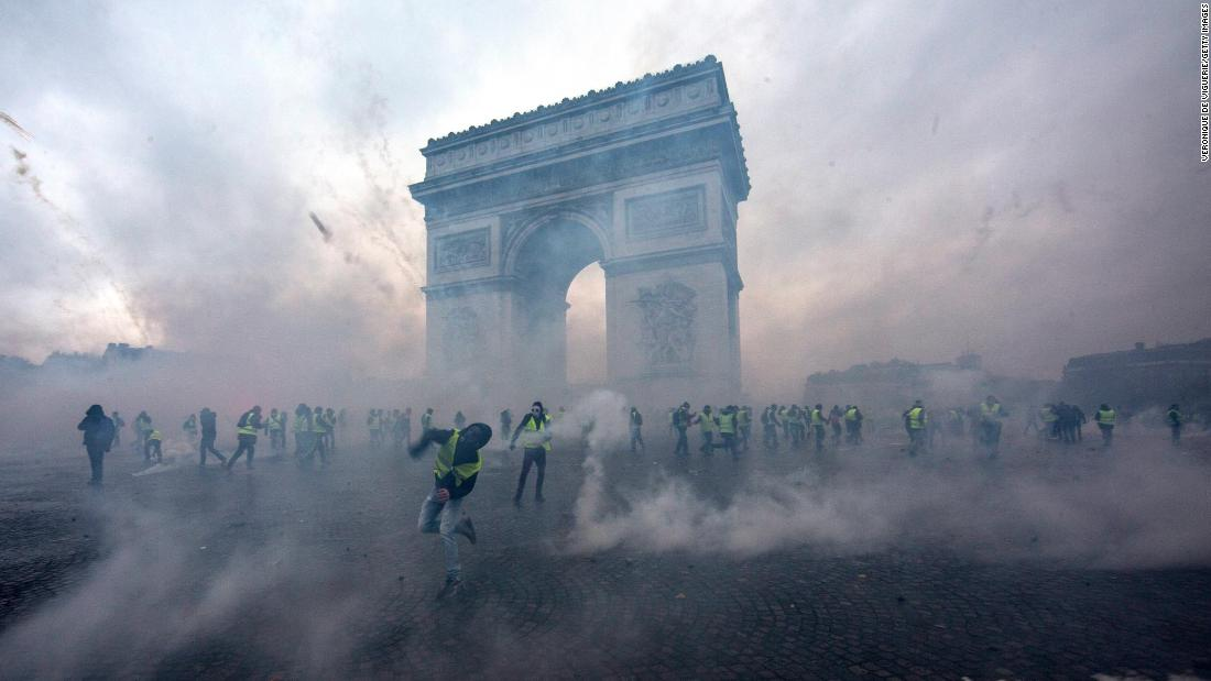 Tear gas surrounds protesters near Paris' Arc de Triomphe as they clash with police on Saturday, December 1. The rising cost of gasoline and diesel fuel sparked protests that have since evolved into broader demonstrations against Emmanuel Macron's government.