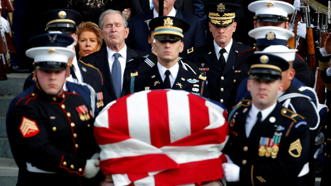 Former US President George W. Bush follows a military honor guard carrying his father's casket after a state funeral in Washington on Wednesday, December 5.
