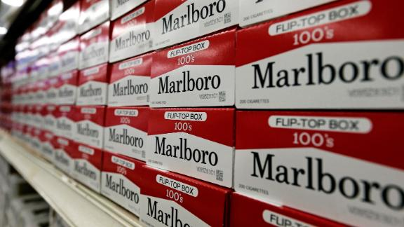 FILE- This June 14, 2018, file photo shows cartons of Marlboro cigarettes on the shelves at JR outlet in Burlington, N.C. Curiosity from one the world's largest tobacco companies about the marijuana business sent shares of a Canadian cannabis company higher at the opening bell Tuesday, Dec. 4. Cronos Group confirmed talks late Monday with Marlboro maker Altria about a possible investment. (AP Photo/Gerry Broome, File)