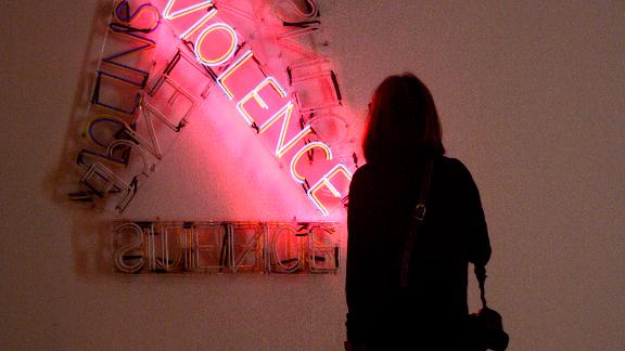 """A museum visitor admires neon artwork by Bruce Nauman titled, """"Violins Violence Silence"""" in London."""