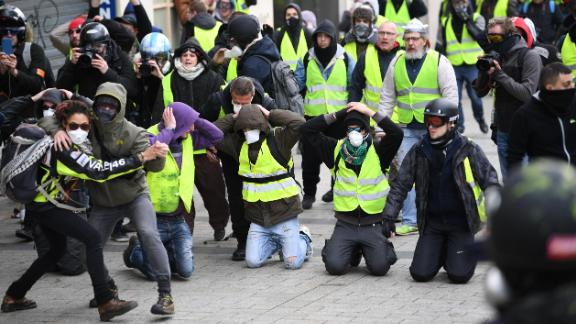 Two demonstrators dance in front a group kneeling and holding their hands on their heads as they take part in the demonstration of the yellow vests at the Arc de Triomphe on December 08, 2018 in Paris France.