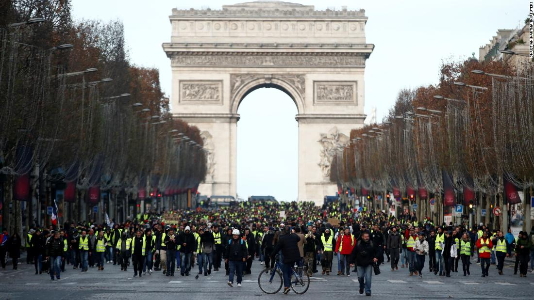 Protesters wearing yellow vests walk on the Champs-Elysees Avenue with the Arc de Triomphe in the background during a protest on December 8.