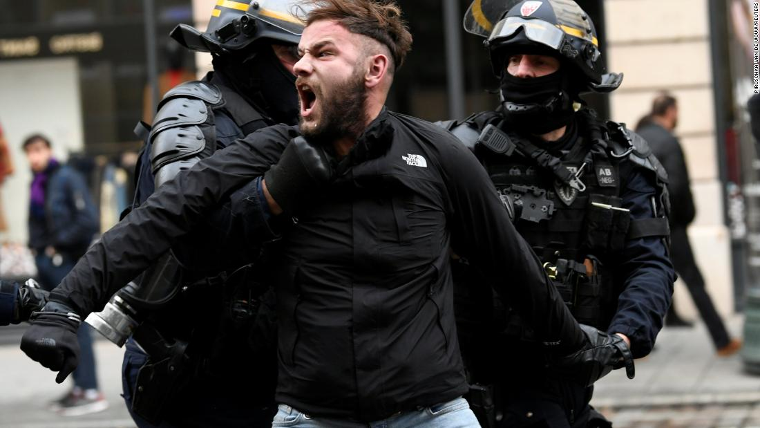 French police apprehend a man on December 8 during a protest in Paris.