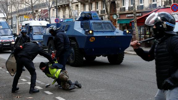 French gendarmes apprehend a protester on December 8 in Paris.