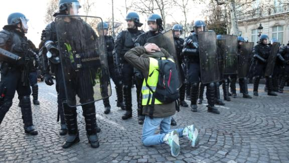 "A protestor wearing a ""yellow vest"" (gilet jaune) kneels  in front of the police forces on the Champs Elysees avenue in Paris on December 8, 2018 during a protest against rising costs of living they blame on high taxes. - Paris was on high alert on December 8 with major security measures in place ahead of fresh ""yellow vest"" protests which authorities fear could turn violent for a second weekend in a row. (Photo by Zakaria ABDELKAFI / AFP)        (Photo credit should read ZAKARIA ABDELKAFI/AFP/Getty Images)"