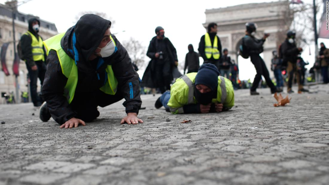 Demonstrators drop flat to the ground on the Champs-Elysees avenue during a protest on Saturday, December 8, in Paris.