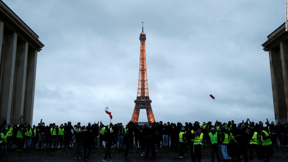Protesters wearing yellow vests gather on December 8 in front of the Eiffel Tower in Paris.