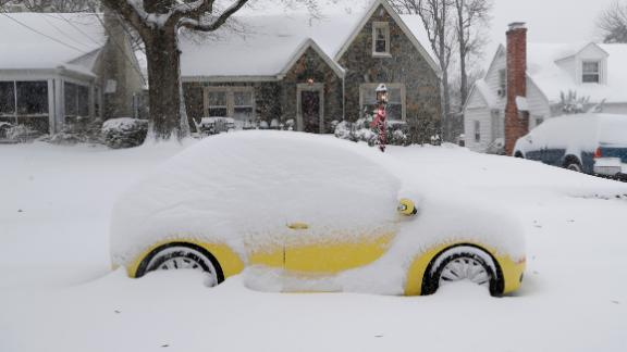 A snow-covered car sits outside a home Sunday in Greensboro, North Carolina.