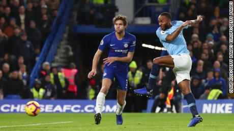 Raheem Sterling of Manchester City shoots as Marcos Alonso of Chelsea looks on during the Premier League match between Chelsea and Manchester City on Saturday.