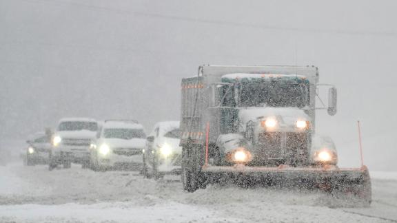A snowplow is followed closely by cars as it clears US 301 in Hanover County, Virginia, on Sunday.