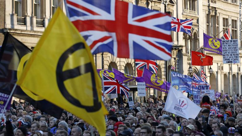Protesters hold up placards and Union flags as they attend a pro-Brexit rally promoted by UKIP in central London on December 9, 2018.