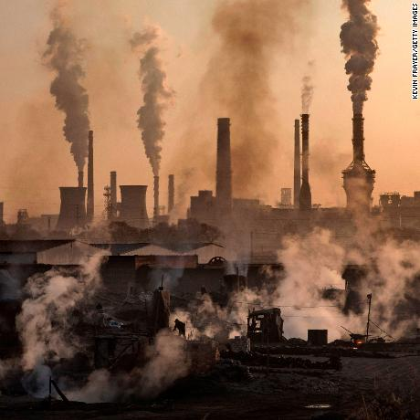 "INNER MONGOLIA, CHINA - NOVEMBER 04: Smoke billows from a large steel plant as a Chinese labourer works at an unauthorized steel factory, foreground, on November 4, 2016 in Inner Mongolia, China. To meet China's targets to slash emissions of carbon dioxide, authorities are pushing to shut down privately owned steel, coal, and other high-polluting factories scattered across rural areas. In many cases, factory owners say they pay informal 'fines' to local inspectors and then re-open. The enforcement comes as the future of U.S. support for the 2015 Paris Agreement is in question, leaving China poised as an unlikely leader in the international effort against climate change. U.S. president-elect Donald Trump has sent mixed signals about whether he will withdraw the U.S. from commitments to curb greenhouse gases that, according to scientists, are causing the earth's temperature to rise. Trump once declared that the concept of global warming was ""created"" by China in order to hurt U.S. manufacturing. ChinaÍs leadership has stated that any change in U.S. climate policy will not affect its commitment to implement the climate action plan. While the world's biggest polluter, China is also a global leader in establishing renewable energy sources such as wind and solar power. (Photo by Kevin Frayer/Getty Images)"