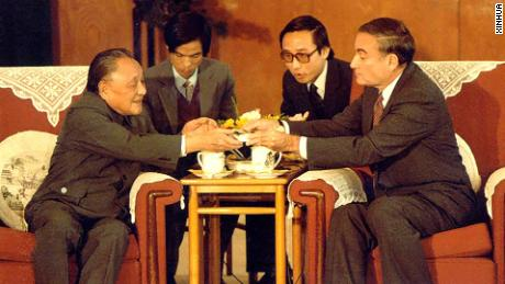 Chinese Paramount Leader Deng Xiaoping meets New York Stock Exchange chairman John Phelan in 1986. Victor Gao is sitting behind Phelan.