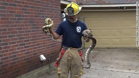 A firefighter in suburban Houston carries two snakes from a burning home.