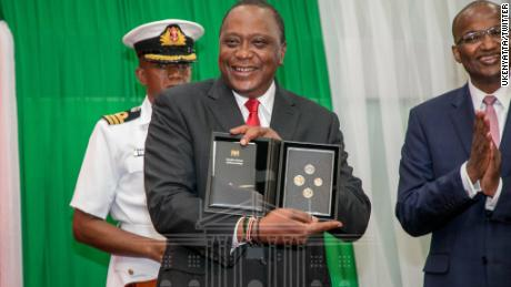 Kenya's President Uhuru Kenyatta unveils the county's new currency coins in Nairobi's capital on December 11, 2018.