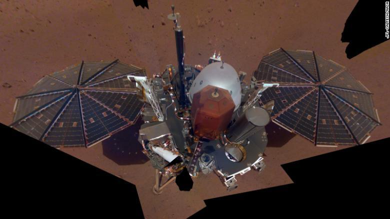 Это первое селфи НАСА InSight на Марсе. На ней отображаются солнечные панели и палуба судна. На верхней части палубы находятся ее научные приборы, штанги датчиков погоды и антенна УВЧ.