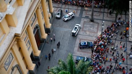 People gather outside the Cathedral of Campina after a man opened fire during mass and killed at least four people before committing suicide on Tuesday.