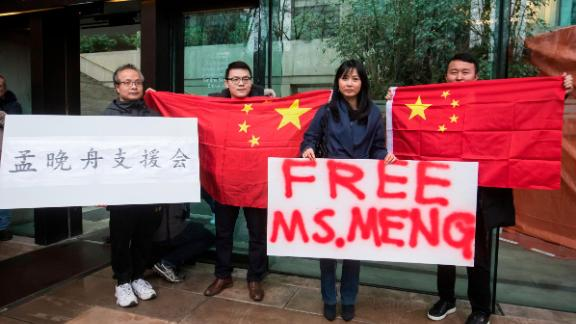 Supporters hold signs and Chinese flags outside court in Canada during the third day of a bail hearing for Meng Wanzhou, the chief financial officer of Huawei.