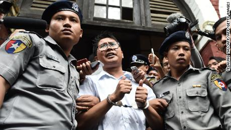Myanmar journalist Wa Lone (C) is escorted by police after being sentenced by a court to jail in Yangon on September 3, 2018.