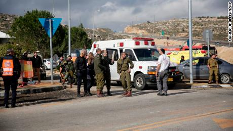 Israeli soldiers stand near the scene of the attack.