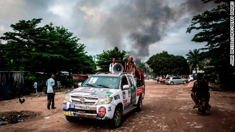 A campaign car rolls on as smoke rises from a fire at the independent national electoral commission's warehouse on December 13, 2018, in Kinshasa, Democratic Republic of Congo.