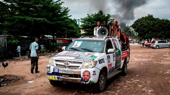 A campaign car rolls on as smoke rises from a fire at the independent national electoral commission
