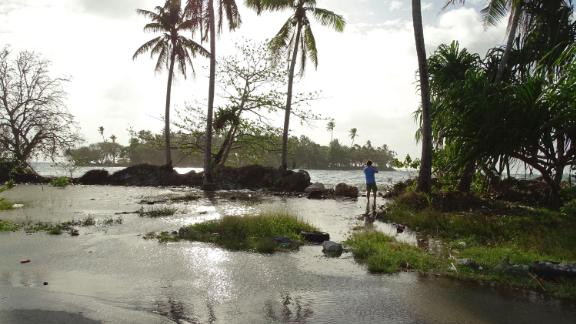In this photo taken on March 9, 2016, a resident walks through tidal water in Majuro Atoll, in the Marshall Islands. Residents in low-lying areas of the Marshall Islands were braced for ongoing flooding on March 11, as a series of inundations underscored the Pacific island nation