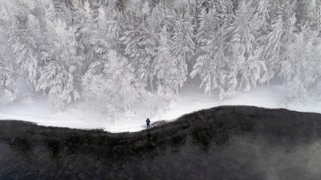 A man fishes on a snow-covered bank of the Yenisei River outside the Siberian city of Krasnoyarsk, Russia, on Monday, December 10.