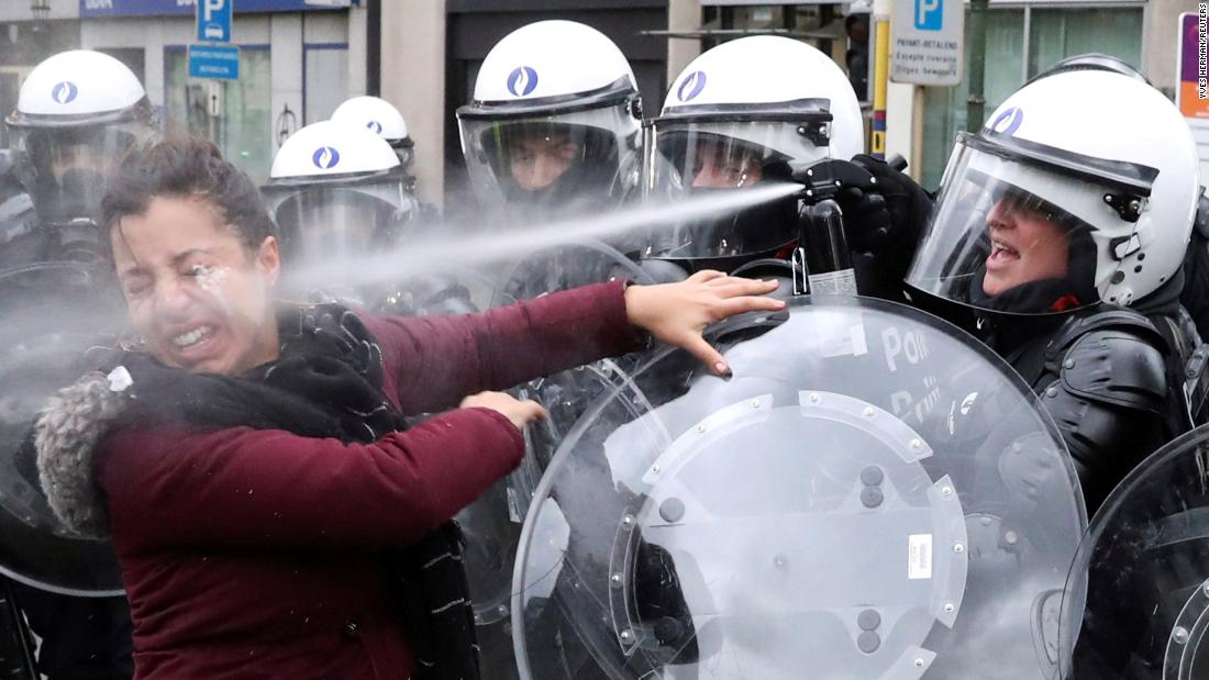 """A woman is sprayed with teargas by a riot police officer during the """"yellow vests"""" protest against higher fuel prices, in Brussels, Belgium, on Saturday, December 8. The smaller demonstration of about 500 people was akin to those held in Paris on December 1."""