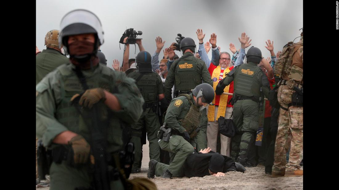 US Border Patrol agents make arrests during a pro-migration protest in San Diego, as seen through the border fence from Tijuana, Mexico on Monday, December 10. Members of various faith groups showed support for Central American asylum-seekers who arrived in recent caravans and called for an end to migrant detentions and deportations.