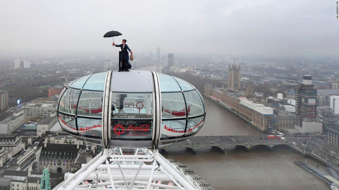 """A Mary Poppins stunt double rides atop of the London Eye on Wednesday, December 12, ahead of the European movie premiere of """" Mary Poppins Returns ."""""""