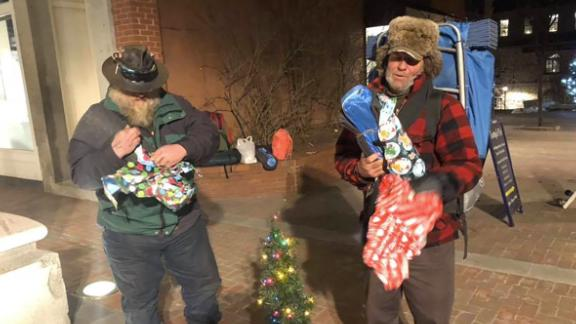 Two homeless men open presents they received from Rodney Smith Jr.